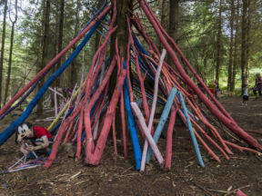 Kids enjoying rainbow den building on the Forest of Dean Sculpture Trail at Beechenhurst, Gloucestershire.