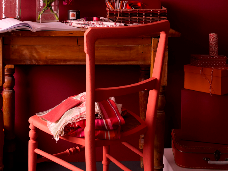 A bold painted chair using Earthborn Riding Hood, a warm red paint colour