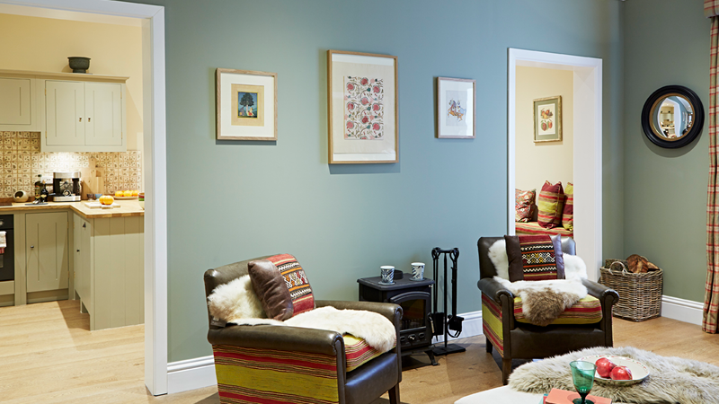 Warm paint colours like Earthborn's soft olive green Sunday Stroll are perfect for dark, north facing rooms