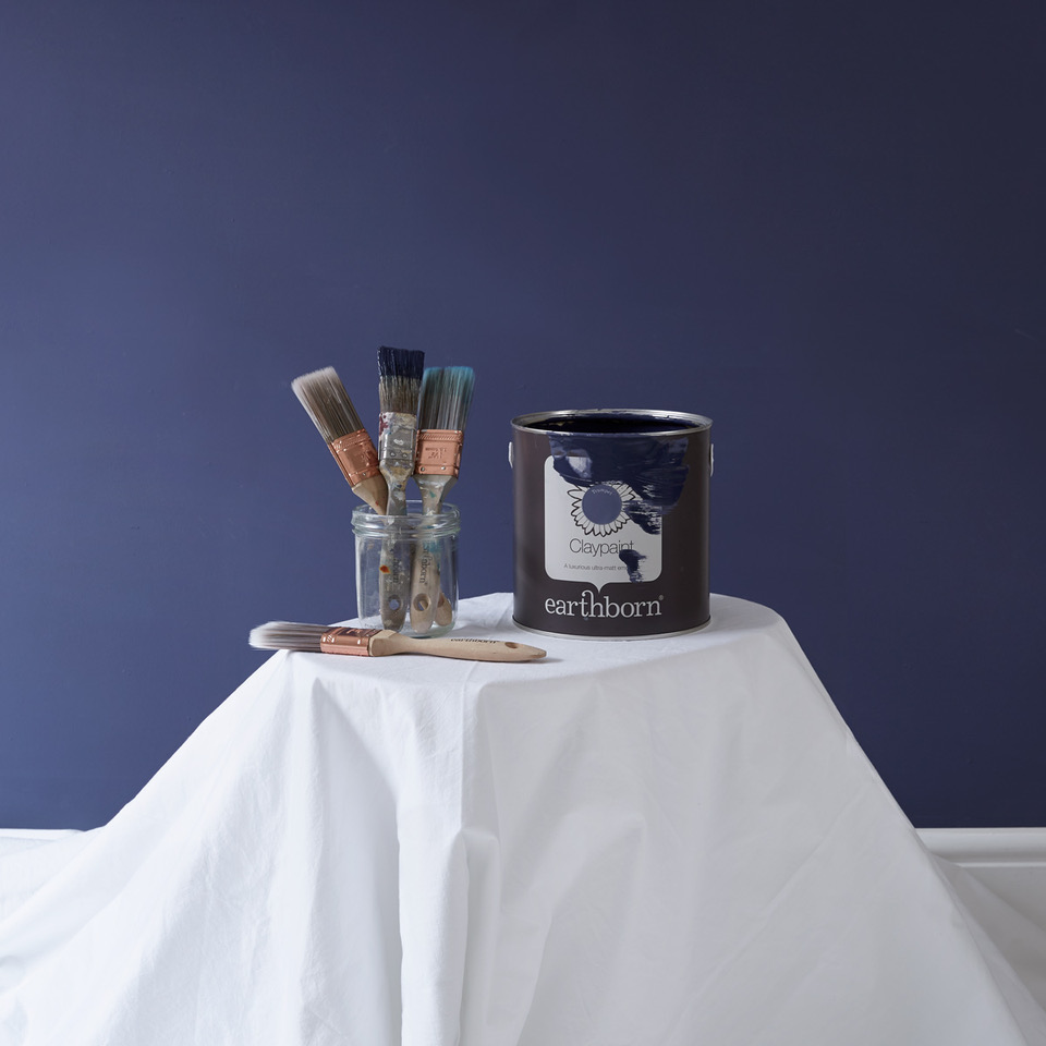 When it comes to painting a room don't forget the dust sheets! This lovely wall colour is Earthborn's Trumpet