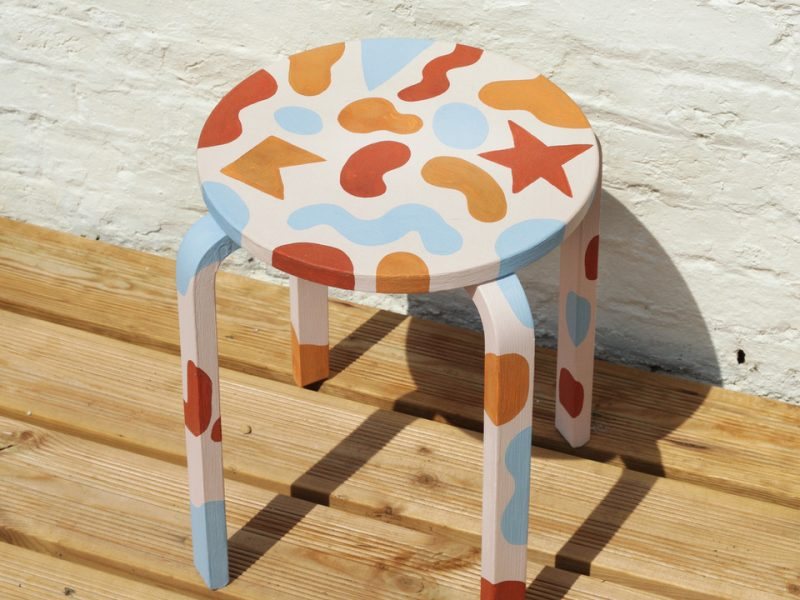 A colourful MDF stool designed by Melanie Johnsson painted in Earthborn colours