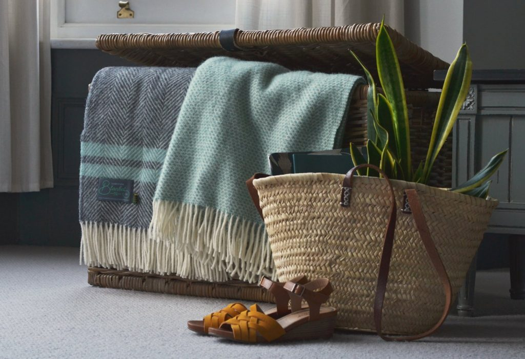 A basket of blankets beside the sofa makes your living room ready for a cosy night in