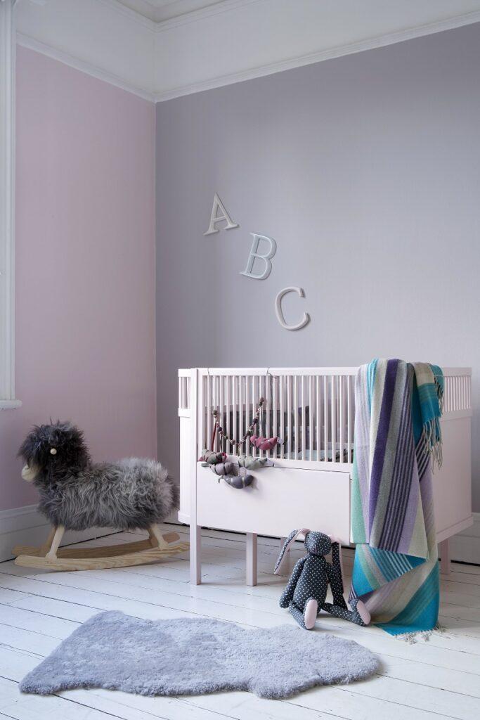 Nursery walls painted in Rosie Posie and Inglenook with cot in Cupcake